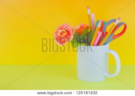 A white mug full of penciles markers scissors and a silk rose on green table with golden background. Copy space available. Good image for administrative professional's day in April