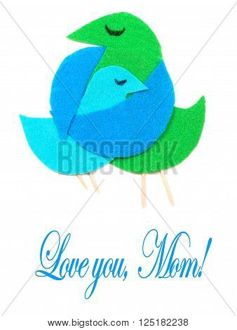 Felt cut out bird shapes in green and blue with toothpick legs and black marker eyes. Mom bird is embracing baby bird. Isolated on white. Mother's Day message.