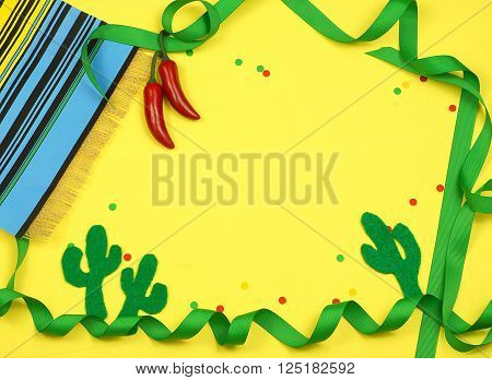 A green ribbon border winds in and out of frame and is decorated with a serape blanket red chilis felt cutout cactus shapes and confetti on a yellow background for Cinco de Mayo in May