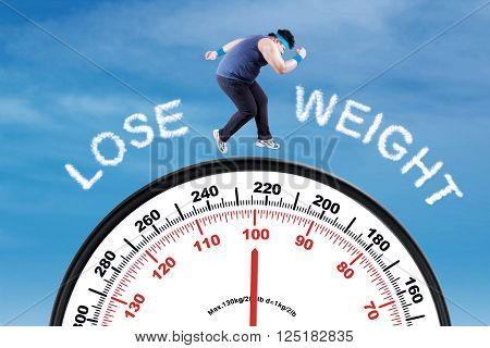 Overweight man running above a scale with text lose weight shot under blue sky