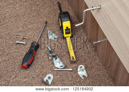 Hand tools for assembling furniture at home, Phillips screwdriver measuring tape, metal brackets, screws and Allen key.
