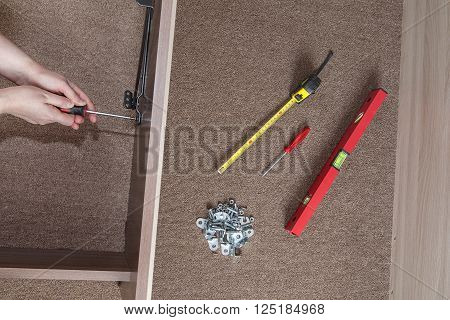 Bed frame assembly furniture builder hands fix the screw using a screwdriver nearby is the tool level tape measure and fasteners.