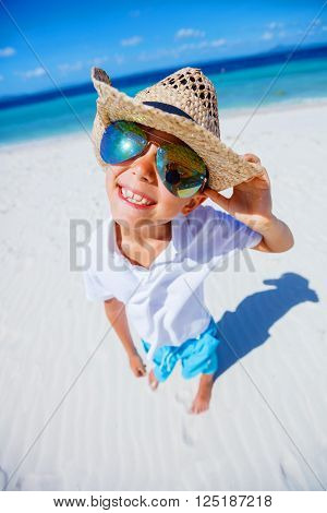 Happy boy in the sunglasses and hat on the tropical white beach