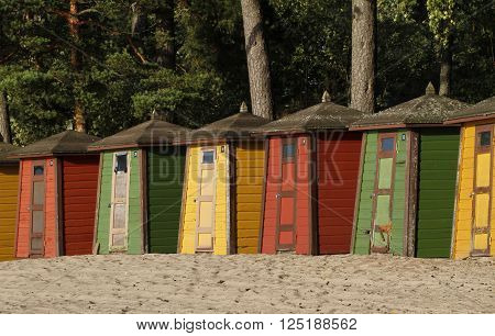 Row of colourful wooden cubicles on the beach of Pihlajasaari in Helsinki, Finland.