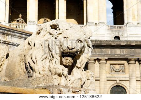 Color DSLR stock image of a carved lion in the fountain in the plaza fronting the Church of Saint-Sulpice, Paris, France.  Ancient Roman Catholic cathedral is popular tourist destination.