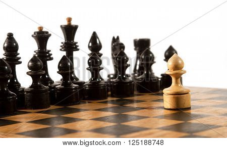 Rows of black chess figures and a single white pawn on the chessboard (isolated on white selective focus on the white pawn)