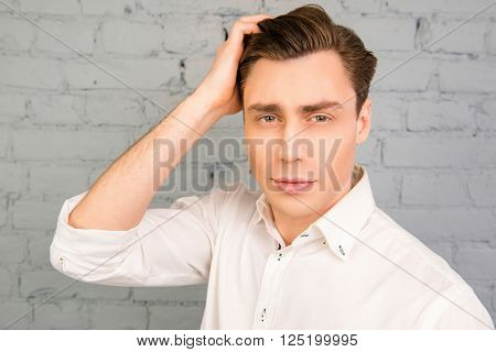 Attractive Man Touching His Hair On The Background Of Gray Wall