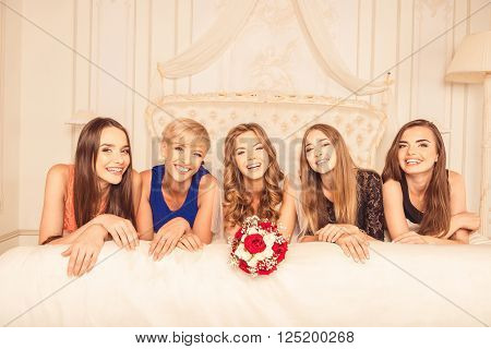 Cute smiling girls lying on bed and celebrating hen-party