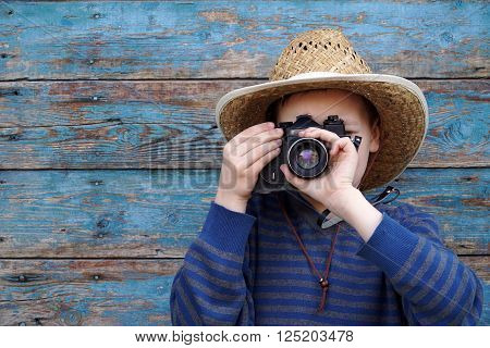 boy in a hat and with a camera at the wooden wall