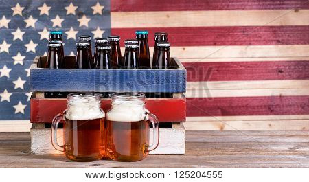 Two pint jars filled with beer crate with unopen bottle and vintage wooden USA flag in background. Holiday party concept.