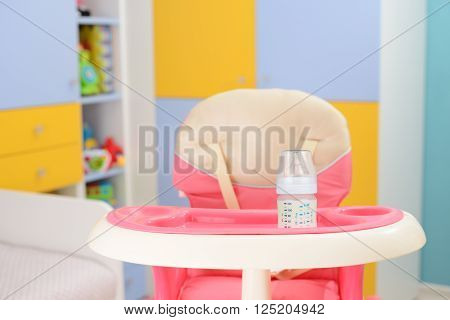 Baby pink high chair and bottle with milk in baby room
