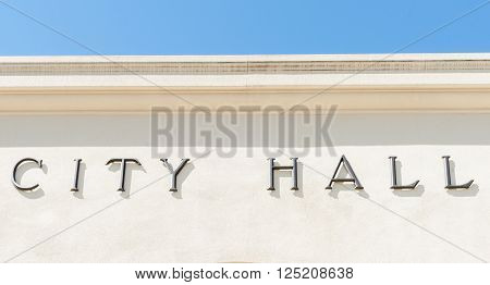 City Hall sign on exterior biege colored wall with blue sky.