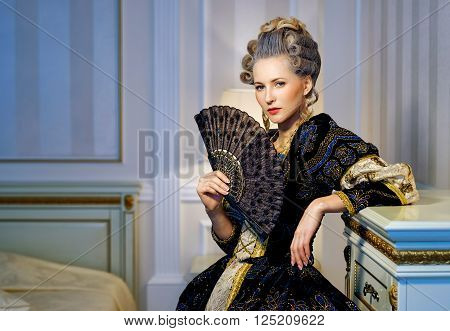 Beautiful woman with fan in historical dress in Baroque style in the interior