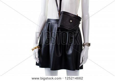 Purse and skirt on mannequin. Retro handbag with leather skirt. Woman's fashionable dark skirt. Gold bracelet and black bag.