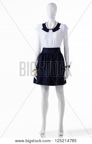 Short sleeve blouse on mannequin. Skirt with short sleeve blouse. Lady's light top and skirt. Woman's bicolor evening outfit.
