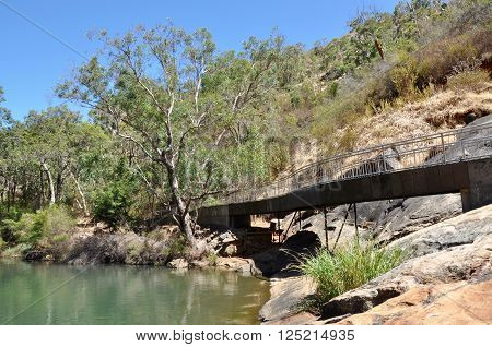 Pedestrian walkway along the natural granite rock cliffs at Serpentine Falls with green rock pools and native flora in Serpentine, Western Australia.