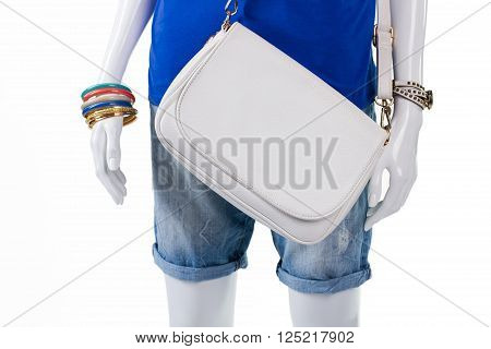 Folded shorts with leather handbag. Simple white bag on mannequin. Colorful bijouterie and plain purse. Inexpensive leather handbag in stock.