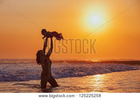 Happy family swimming fun on sea beach - mother tossing up baby son into mid air catching on sunset sky sun background Parents outdoor activity child lifestyle on summer vacation in tropical island