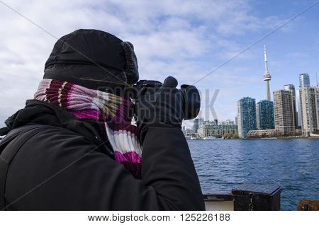 Toronto Canada - January 27 2016: Person taking photos of Toronto skyline from a ship Ontario Canada.