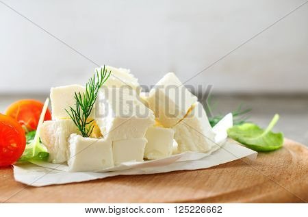 Slices feta cheese with dill, cherry tomatoes and spinach leaves on a wooden board closeup