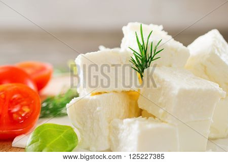 Slices feta cheese with dill and cherry tomatoes closeup