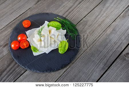 Sliced feta cheese with dill, cherry tomatoes and spinach leaves on wooden table on a black ceramic board