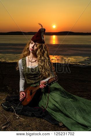 Girl in medieval dress and hat on the lake shore with a lute. Sunset.