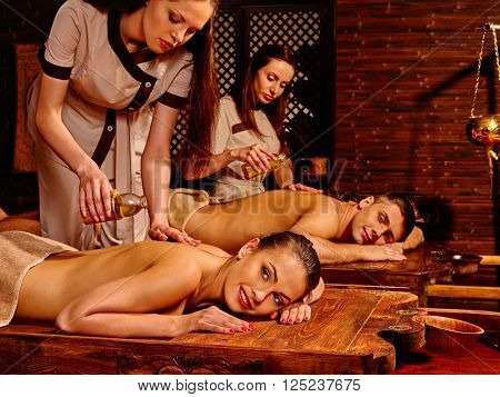 Loving couple  with a soothing ayurvedic spa treatment. Oil massage in  Spa salon. Spa salon decoreted bamboo.