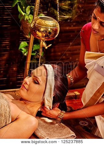 Woman with Shirodhara make pouring oil on the head of a spa in India. Preparatory procedures.