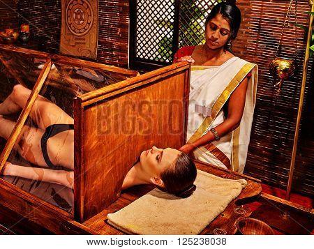 Woman having Ayurvedic sauna treatment. She relaxed. Preparatory procedures.