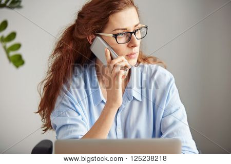 Portrait of a young office female worker wearing glasses, sitting at her working table with a serious look and talking on her cell phone. Young businesswoman discussing working plans in her office.