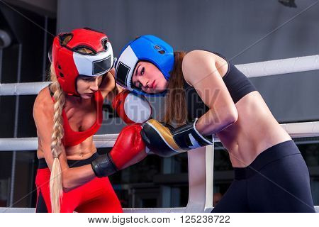 Two  women boxer wearing red  gloves and helmet to box in ring. girls beat each other. Boxing.