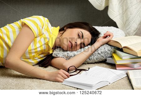 Young woman fell asleep while reading books on the floor