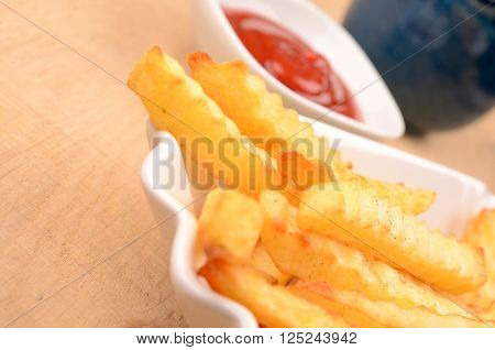French fries with tomato sauce in a white bowl