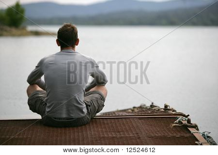 Young man sitting on a pontoon by a lake