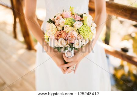 Bride boho style. Only visible hand with a bouquet and white dress. Bouquet of roses. The girl flowing white dress photographed in nature.