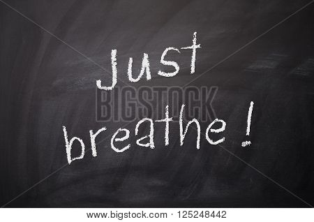 Chalkboard with the words Just breathe! wellness and health care concept