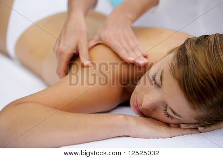 Beautiful woman with eyes closed having a body massage