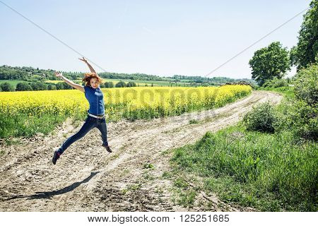 Joyful caucasian woman is jumping in rapeseed field. Beauty fashion and nature. Vibrant colors.