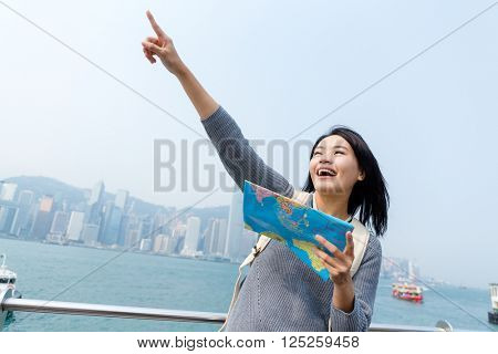 Woman looking far away and holding map in Hong Kong