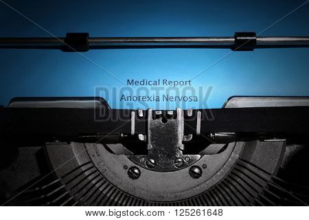 Old typewriter and inserted blue sheet of paper with medical report on anorexia