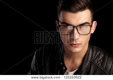 closeup portrait of shaved macho man in black leather jacket and white shirt wearing glasses while looking at the camera in isolated black studio background