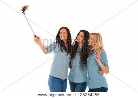 3 casual young women taking a selfie with their phone , one is making the votcory sign, on white background