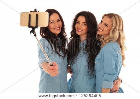 3 smiling women taking a selfie photo with their phone on white studio background
