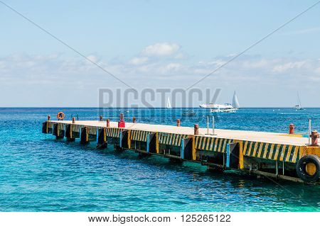 Concrete Pier with Boats in Background in Cozumel