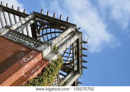 Looking up at pergola at angle with blue sky in background