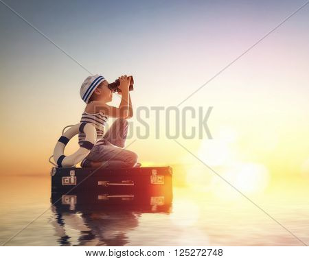 Dreams of travel! Child floats on a suitcase against the backdrop of a sunset.