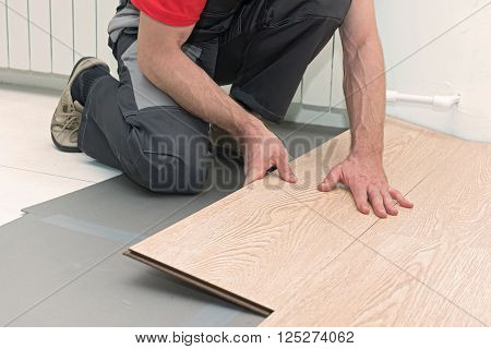 Man installing new laminated wooden floor ni the room
