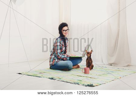 Young girl in computer glasses on a carpet with laptop and dog chihuahua. Hipster freelancer woman works at home. Home office, freelance. Brunette with laptop in modern interior. Soft tone, high key.
