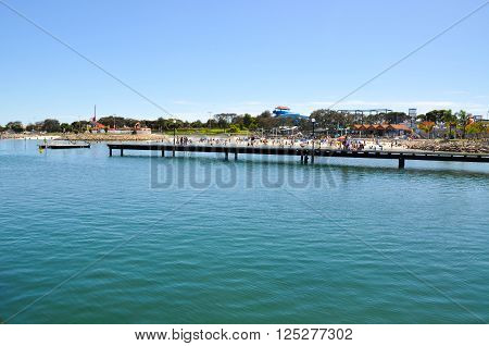 HILLARYS,WA,AUSTRALIA-JANUARY 22,2016: Jetty and cove with tourists on the beach at Hillarys Boat Harbour in Hillarys, Western Australia.